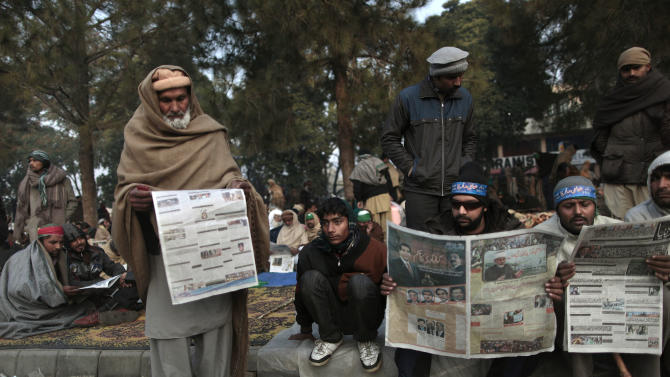 Supporters of Pakistani Sunni Muslim cleric Tahir-ul-Qadri, read local newspapers, one of them featuring an image of Pakistan's Prime Minister Raja Pervaiz Ashraf, as they camp near parliament, during an anti-government rally in Islamabad, Pakistan, Wednesday, Jan. 16, 2013. Pakistan's leaders received a powerful one-two punch Tuesday as the Supreme Court ordered the arrest of the prime minister in a corruption case and the firebrand cleric led thousands of protesters in another day of anti-government demonstrations in the capital. (AP Photo/Muhammed Muheisen)