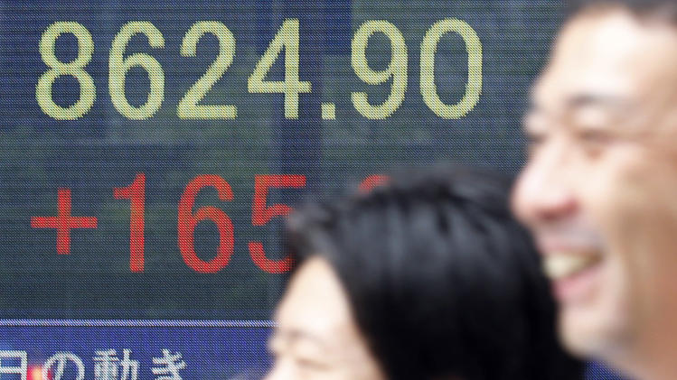 People walk by an electronic stock board of a securities firm in Tokyo, Monday, June 11, 2012 as Japan's Nikkei 225 index jumped 165.64 points and closed at 8,624.90. Asian stocks and the euro climbed Monday after Spain sought a lifeline for its ailing banks, easing fears that Europe's debt crisis was about to spin out of control. (AP Photo/Koji Sasahara)