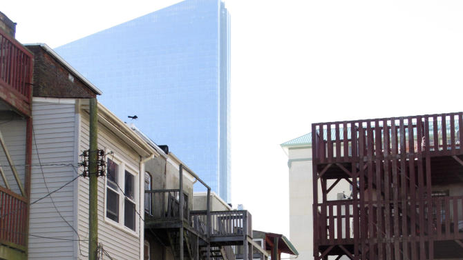 In this Monday, Nov. 12, 2012 photo, Eddie Santiago carries a wrecked door to the curb at a friend's house in Atlantic City, N.J., in the shadow of Revel, the city's newest casino. Two weeks after Superstorm Sandy hit the region, many of Atlantic City's poorest residents are enduring its aftermath with quiet acceptance and gratitude for the help being offered to them. (AP Photo/Wayne Parry)