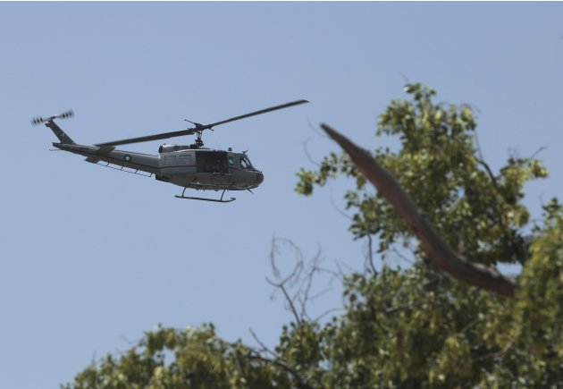 A military helicopter flies overhead as police officers and soldiers secure the area before the motorcade of Chinese Premier Li passes by in Islamabad