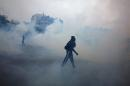 Demonstrators walk in the smoke of tear gas during a protest against proposed changes to France's work week and layoff practices, in Paris, Saturday, April 9, 2016. Protesters across France are marching to voice their anger at labor reforms being championed by the country's Socialist government. (AP Photo/Thibault Camus)