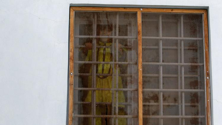 An Afghan girl looks out of a window at Herat's prison for women, western Afghanistan