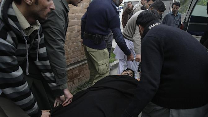 People carry the body of a police officer into an ambulance in Mardan. Pakistan, Tuesday, Feb. 26, 2013. Police say gunmen have shot dead a police officer protecting a team of polio workers during a U.N.-backed vaccination campaign in northwestern Pakistan. (AP Photo/Sohail Iqbal)