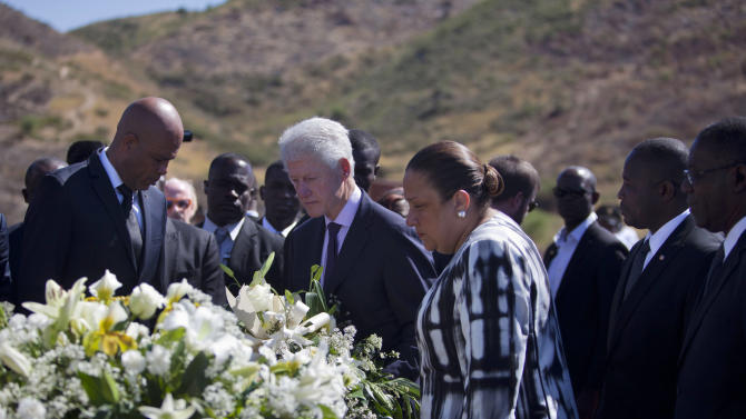 Haiti's President Michel Martelly, left, UN special envoy to Haiti and former President Bill Clinton, center ,and Haiti's first lady Sophia Martelly, right center, attend a memorial service for victims of the 2010 earthquake, at Titanyen, a mass burial site north of Port-au-Prince, Haiti, Saturday, Jan. 12, 2013. Haitians recalled the tens of thousands of people who lost their lives in a devastating earthquake three years ago, marking the disaster's anniversary Saturday with a simple ceremony. Haiti's previous presidential administration said 316,000 people were killed but no one really knows how many died.  (AP Photo/Dieu Nalio Chery)