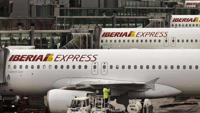 "A man works on an Iberia jet while passengers wait to board another plane, in a parking zone at Barajas international airport in Madrid, Friday, Nov. 9, 2012. International Airlines Group on Friday warned that its Spanish carrier Iberia was ""in a fight for survival"" and unveiled a restructuring plan to cut 4,500 jobs as it reported a drop in third-quarter profit. (AP Photo/Daniel Ochoa de Olza)"