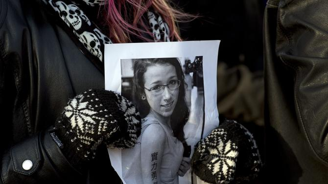 A woman holds a photo as several hundred people attend a community vigil to remember Rehtaeh Parsons at Victoria Park in Halifax, Nova Scotia on Thursday, April 11, 2013. The girl's family says she ended her own life last week following months of bullying after she was allegedly sexually assaulted by four boys and a photo of the incident was distributed. (AP Photo/The Canadian Press, Andrew Vaughan)