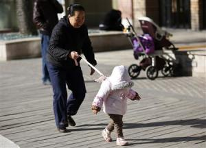 A woman holds onto a safety string attached to the back of a child at a shopping mall in Beijing