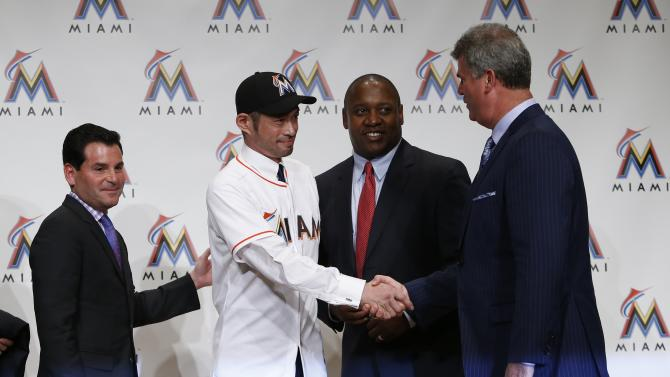 Japan's outfielder Ichiro Suzuki, wearing his new Marlins hat and jersey, shakes hands with Miami Marlins General Manager Dan Jennings during a news conference to announce an agreement on a one-year contract with the Miami Marlins, in Tokyo