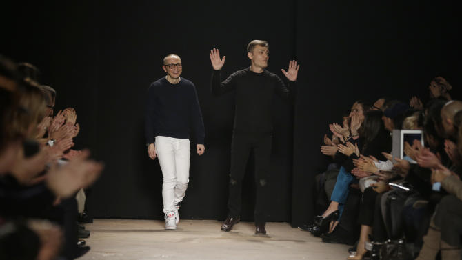 Italian fashion designers Tommaso Aquilani, left, and Roberto Rimondi are seen on the catwalk at the end of their women's Fall-Winter 2013-14 fashion show, part of the Milan Fashion Week, unveiled in Milan, Italy, Saturday, Feb. 23, 2013. (AP Photo/Luca Bruno)