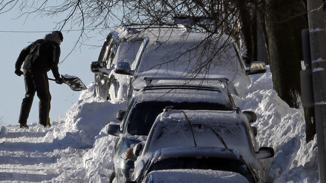 A man shoves his car out of the snow on M street in the South Boston neighborhood of Boston, early Sunday, Feb. 10, 2013. (AP Photo/Gene J. Puskar)
