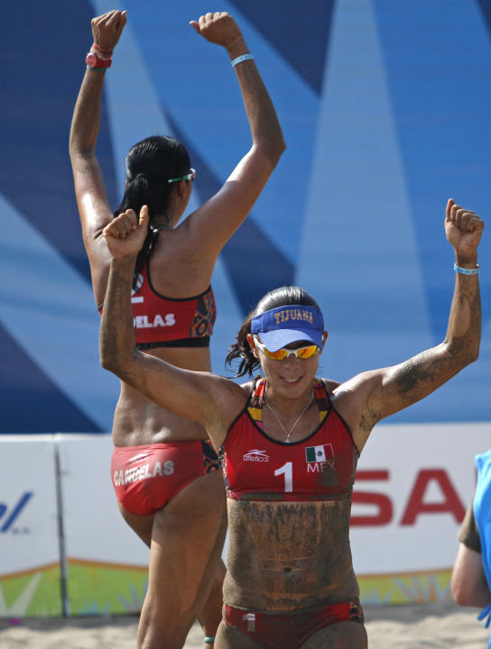 Mexico's Mayra Garcia, front, and teammate Bibiana Candelas celebrate after wining a women's beach volleyball match against Uruguay at the Pan American Games in Puerto Vallarta, Mexico, Tuesday, Oct.