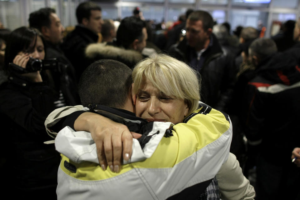 A Serbian woman is greeted by a member of her family as she arrives from Tripoli, Libya to Belgrade, Serbia, Wednesday, Feb. 23, 2011. The Serbian government sent three planes to Libya on Wednesday to evacuate Serbian citizens who wanted to leave the country due to the current uprising. (AP Photo/ Marko Drobnjakovic)