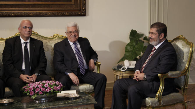 Palestinian negotiator Saed Erakat, left, and Palestinian President Mahmoud Abbas, center, meet with Egyptian President Mohammed Morsi, right, at the presidential palace in Cairo, Egypt, Wednesday, July 18, 2012. (AP Photo/Maya Alleruzzo)