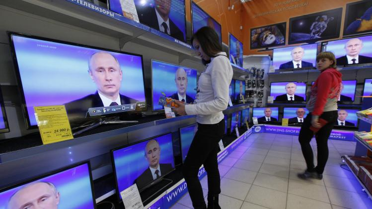 Women stand near TV sets during Russian President Putin's live broadcast nationwide phone-in at the DNS electronic shop in Russia's Siberian city of Krasnoyarsk