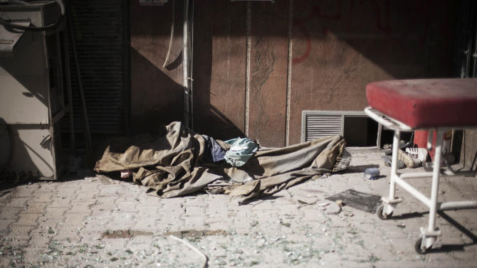 In this Wednesday, Sept. 19, 2012 photo, the body of an elderly man, said by rebels to be a Coptic Christian, lies at the door of a hospital controlled by the Free Syrian Army in Aleppo, Syria.(AP Photo/Manu Brabo)