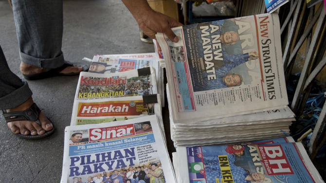 A man reaches down to buy a local newspaper featuring results of Malaysia's general elections, in Kuala Lumpur, Malaysia, Monday, May 6, 2013. Malaysia's long-governing coalition, Prime Minister Najib Razak's National Front coalition, won the national election with a weakened majority to extend its unbroken 56-year rule. (AP Photo/Mark Baker)