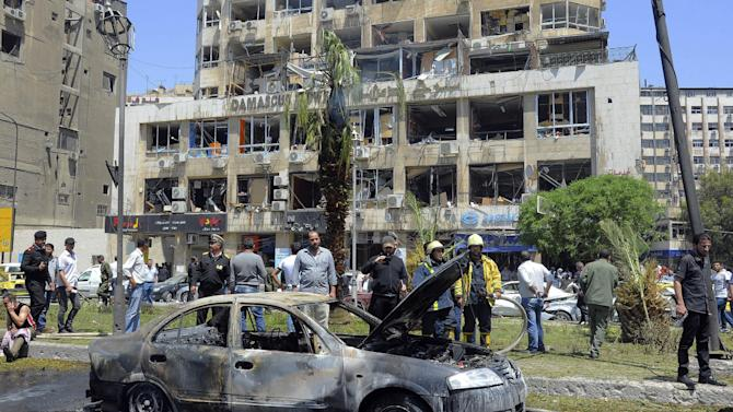 In this photo released by the Syrian official news agency SANA, Syrian security officers gather in front of a burned car, at the scene where a powerful explosion occurred at the central district of Marjeh, in Damascus, Syria, Tuesday April 30, 2013. A powerful explosion rocked Damascus on Tuesday, causing scores of casualties, a day after the country's prime minister narrowly escaped an assassination attempt in the heart of the heavily protected capital. (AP Photo/SANA)