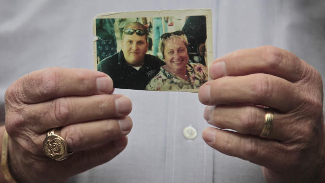 Ken Fairben holds a photo showing his son Keith, left, a victim of the Sept. 11, 2001 attacks, posing with his mother Diane Fairben, as he holds a press briefing on Monday, Oct. 15, 2012, outside Fort Hamilton Army base in Brooklyn, N.Y.  Military installations in New York, New Jersey, Massachusetts and Maryland are welcoming families of 9/11 victims this week to watch pretrial hearings in Cuba for five men charged in the terrorist attacks via closed-circuit television.  (AP Photo/Bebeto Matthews)