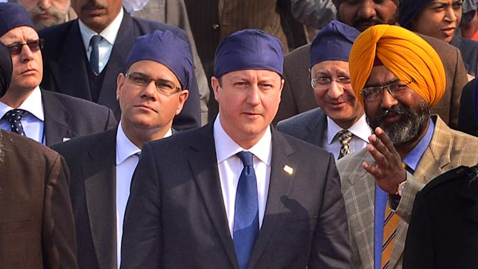 British Prime Minister David Cameron, center, walks barefoot during his visit to the Golden Temple, Sikh's holiest shrine, in Amritsar, India, Wednesday, Feb. 20, 2013. Cameron also laid a mourning wreath at Jallianwala Bagh, the site of a notorious 1919 massacre of hundreds of Indians by British colonial forces. More than 300 Indians were killed during the massacre on unarmed Indians attending a rally, which galvanized the national independence movement. (AP Photo/Sanjeev Syal)