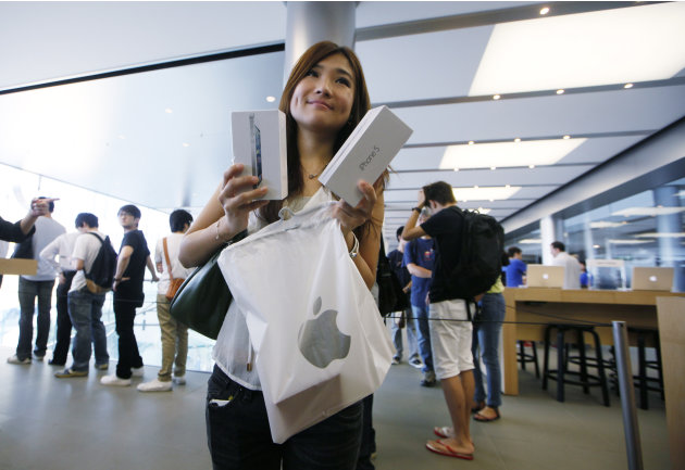 A customer shows her new iPhone 5 at the Apple store in Hong Kong Friday, Sept. 21, 2012. Apple's Asian fans jammed the tech juggernaut's shops in Australia, Hong Kong, Japan and Singapore to pick up 