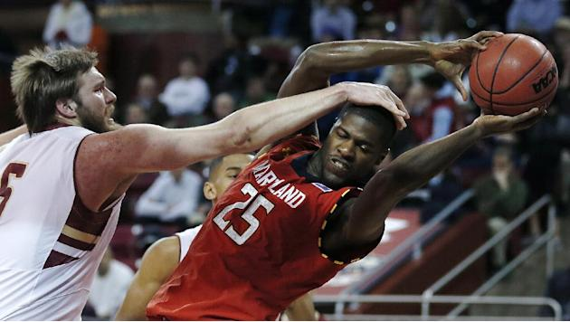 Boston College center KC Caudill, left, reaches to a rebound against Maryland forward Jonathan Graham (25) during the first half of an NCAA basketball game on Thursday, Dec. 12, 2013, in Boston