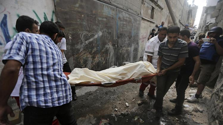 Palestinian carry a dead body found under the rubbles of a home destroyed by an Israeli strike in the Shajaiyeh neighborhood of Gaza City, northern Gaza Strip, Sunday, July 20, 2014. Hundreds of panicked residents have fled the neighborhood which they say has come under heavy tank fire from Israeli forces. Some reported seeing dead and wounded in the streets, with ambulances unable to reach the area. Israel widened its ground offensive early Sunday, sending more troops into the Hamas-ruled territory to destroy tunnels used by the Islamic militants to try to sneak into Israel. (AP Photo/Hatem Moussa)