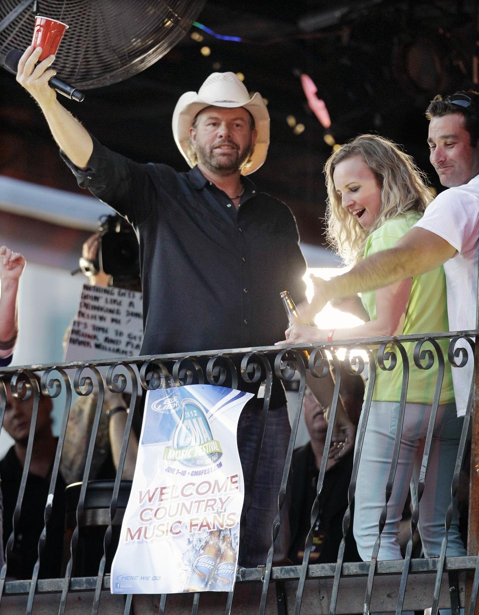 Toby Keith, left, acknowledges the crowd as he stands on a restaurant terrace to introduce an act during the CMT Music Awards show on Wednesday, June 6, 2012, in Nashville, Tenn. (AP Photo/Mark Humphrey)