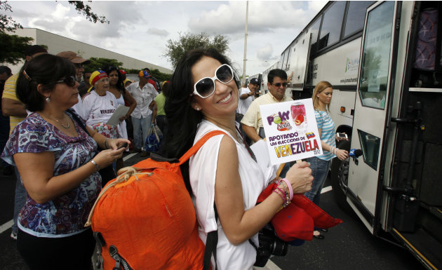 Adrea Leon holds a sign saying she supports the elections in Venezuela as she boards one of fifty buses traveling to New Orleans from Miami to vote in the Venezuelan election  Saturday Oct. 6th, 2012.