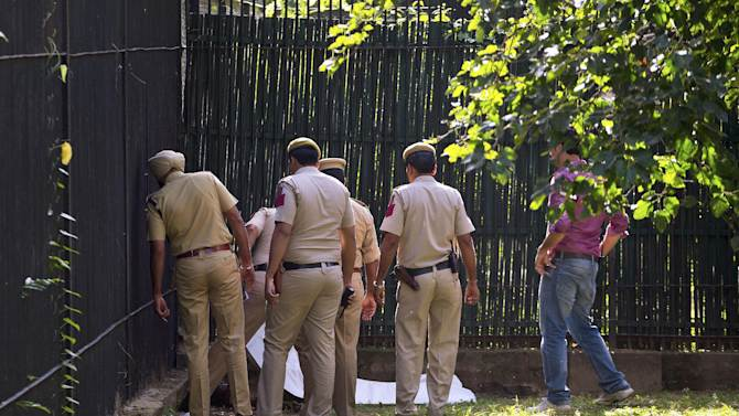 Policemen inspect the body of a man who was killed by a white tiger at the zoo in New Delhi, India, Tuesday, Sept. 23, 2014. The white tiger killed the man who climbed over a fence and jumped into the animal's enclosure Tuesday, a spokesman said. (AP Photo/Saurabh Das)