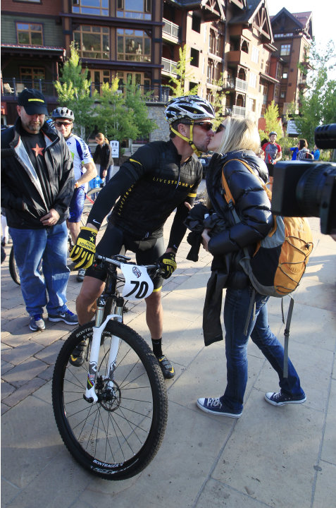 Lance Armstrong kisses girlfriend Anna Hansen as Armstrong prepares to take part in the Power of Four mountain bicycle race at the starting line in Snowmass Village, Colo., early Saturday, Aug. 25, 20