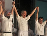 Singapore Prime Minister Lee Hsien Loong (C) of the People's Action Party (PAP) joins hands with some of his candidates as they celebrate victory in the general election in Singapore. Singapore's PAP was returned to power on Sunday with a huge majority but suffered a drop in popularity and lost a key district to a resurgent opposition