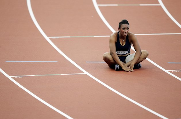 In this Sunday, Aug. 5, 2012 photo, Syria&#39;s Ghfran Almouhamad sits in her lane after a women&#39;s 400-meter hurdles qualifying race during the athletics in the Olympic Stadium at the 2012 Summer Olympics, London. The IOC said Saturday Aug. 11, 2012 that 400-meter hurdler Almouhamad tested positive for the banned stimulant methylhexaneamine on Aug. 3. The backup &quot;B&quot; sample confirmed the positive finding. The 23-year-old athlete finished eighth and last in her first-round heat on Aug. 5. The IOC said she has been disqualified and stripped of her Olympic accreditation. (AP Photo/Matt Slocum)