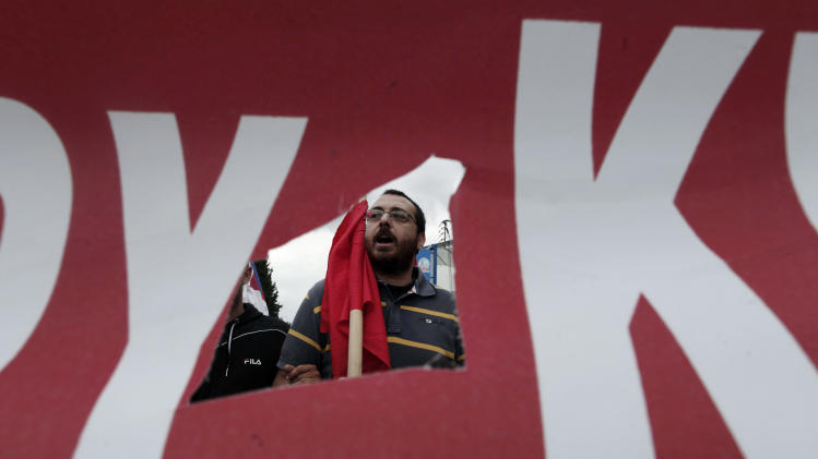 A protester, seen through a hole in a banner, takes part in a rally outside the Greek state television ERT headquarters during a 24-hour general strike in Athens, on Thursday, June 13, 2013. Greece's fragile governing coalition failed to reach a compromise Wednesday about the closure of the state-run ERT broadcaster. That left the government in a crisis that could lead to early elections, just a year after it was formed to save the country from bankruptcy. (AP Photo/Petros Giannakouris)