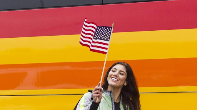 The U.S. women's national soccer team's Alex Morgan waves a U.S. flag as the team arrives at Los Angeles International Airport, Monday, July 6, 2015. The team defeated Japan 5-2 during Sunday's FIFA Women's World Cup in Vancouver. (AP Photo/Ringo H.W. Chiu)