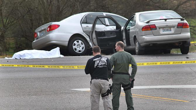 Authorities stand watch over a scene where a body lies covered with a sheet on Hwy 78 in Oxford, Ala., Saturday, Dec. 15, 2012.  Police officers in eastern Alabama shot an assailant armed with an AK-47 assault rifle toward the end of a pursuit that left several people injured, authorities said. The pursuit began after a shooting in Cleburne County. The county is near the Georgia state line. The person in the road was killed by police after leading them on a high speed chase after shooting several people. (AP Photo/Anniston Star, Stephen Gross)