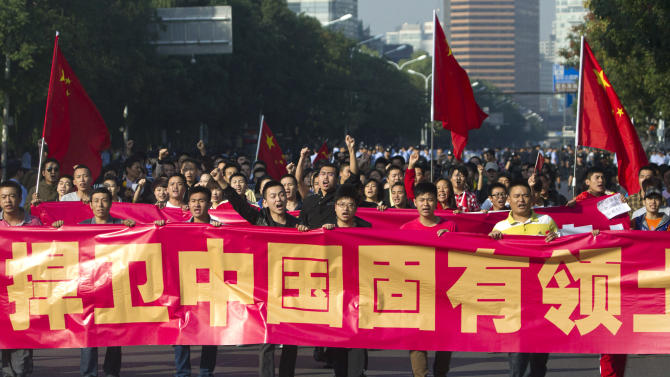 """Anti-Japan protesters hold a banner that reads """"Protect China's inseparable territory"""" as they march on a road outside the Japanese Embassy in Beijing Sunday, Sept. 16, 2012. Security personnel outnumbered the crowds of Chinese protesting against Japan outside its embassy on Sunday, a day after demonstrations over islands that both nations claim spread across China and turned violent. (AP Photo/Alexander F. Yuan)"""
