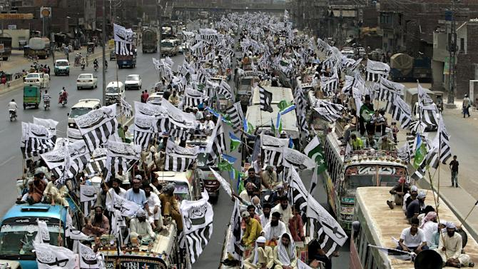 Supporters of the Defense Council of Pakistan sit on the top of vehicles with party flags as they take part in a rally, in Lahore, Pakistan, Sunday, July 8, 2012. Prominent hardline Islamists led thousands of people in a protest against Pakistan's decision to allow the U.S. and other NATO countries to resume shipping troop supplies through the country to Afghanistan. (AP Photo/K.M. Chaudary)