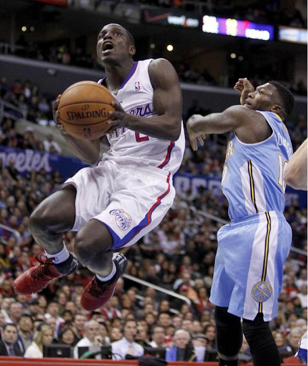 Los Angeles Clippers guard Darren Collison, left, gets past Denver Nuggets guard Nate Robinson on the way to the basket during the first half of an NBA basketball game in Los Angeles on Saturday, Dec.