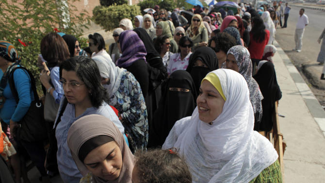 Egyptian women wait for the opening of their polling station on the first day of the presidential runoff, in Cairo, Egypt Saturday, June 16, 2012. Egyptians voted Saturday in the country's landmark presidential runoff, choosing between Hosni Mubarak's ex-prime minister and an Islamist candidate from the Muslim Brotherhood after a race that has deeply polarized the nation. The two-day balloting will produce Egypt's first president since a popular uprising last year ousted Mubarak, who is now serving a life sentence. (AP Photo/Nasser Nasser)