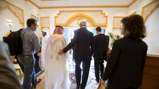 U.S. Secretary of State John Kerry, center, walks through the airport with Ambassador Ibrahim Fakhroo, Qatari Chief of Protocol, left, after being greeted on arrival in Doha, Qatar, on Saturday, June 22, 2013. Kerry began an overseas trip plunging into two thorny foreign policy problems facing the Obama administration: unrelenting bloodshed in Syria and efforts to talk to the Taliban and find a political resolution to the war in Afghanistan. (AP Photo/Jacquelyn Martin, Pool)