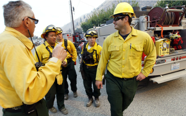 Firefighters get instructions as they ready to head toward a wildfire near the end of Number 1 Canyon Road Monday, Sept. 10, 2012, near Wenatchee, Wash. Crews in central Washington and Wyoming worked