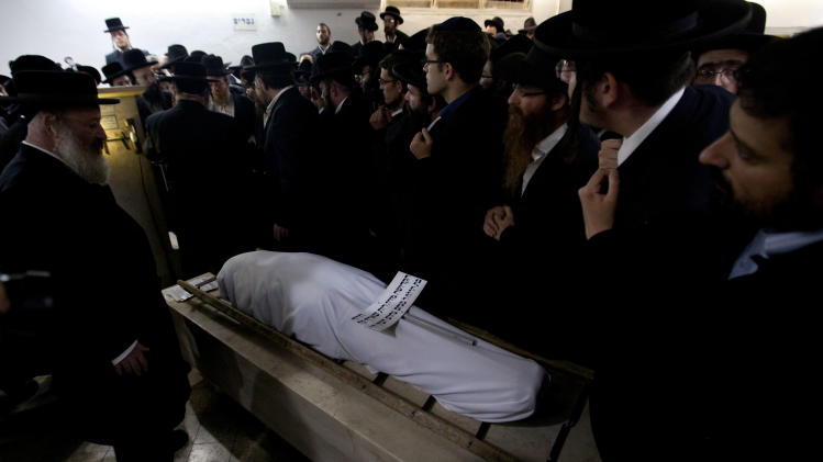 Ultra Orthodox Jewish men gather around the body of Mirah Sharf who was killed in the southern town of Kiryat Malachi by a rocket thought to have been fired by Palestinian militants from the Gaza Strip,  during her funeral in Jerusalem, Thursday, Nov. 15, 2012. Gaza militants led by the ruling Hamas Islamic group showered Israel with rockets in an unprecedented assault Thursday, killing three Israelis and trying for the first time to strike Tel Aviv, the densely populated heart of the Jewish state. (AP Photo/Sebastian Scheiner)