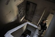 A Syrian rebel looks inside a house during clashes with government forces in the Saif al-Dawla district of the northern city of Aleppo