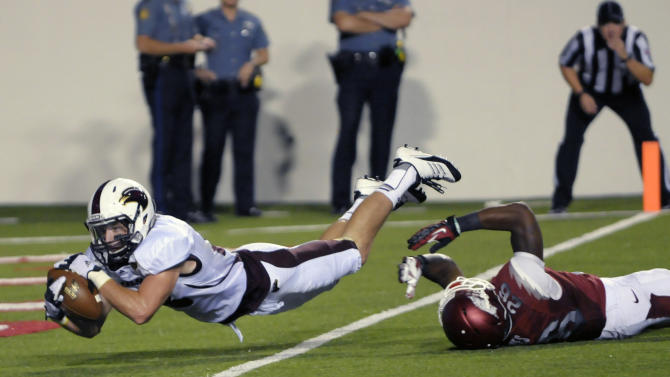 Louisiana Monroe wide receiver Brent Leonard, left, dives past Arkansas safety Rohan Gaines for a 23-yard touchdown with 47 seconds left in regulation to send the game into overtime in an NCAA college football game in Little Rock, Ark., Saturday, Sept. 8, 2012. Louisiana-Monroe defeated Arkansas 34-31 in overtime. (AP Photo/David Quinn)
