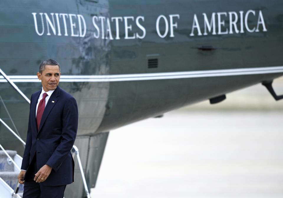 President Barack Obama pauses while walking from Air Force One to Marine One, background, at Andrews Air Force Base, Md., Wednesday, Dec. 14, 2011. (AP Photo/Cliff Owen)