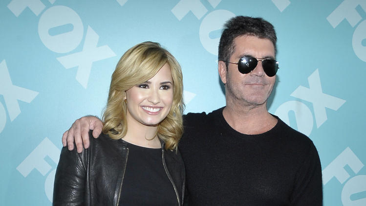 Singer Demi Lovato and Simon Cowell arrive at the 2013 FOX Programming Presentation Post Party at Wollman Rink in Central Park on Monday, May 13, 2013 in New York, New York. (Photo by Andrew Marks/Invision for FOX/AP Images)