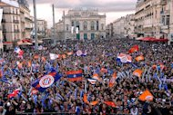 Montpellier's fans wave flags as they wait in front of a giant screen to watch the broadcast of French Ligue 1 match Montpellier vs Auxerre, on May 20, at the place de la Comedie in Montpellier, southern France. Montpellier claimed the first league title in their history after winning the match 2-1