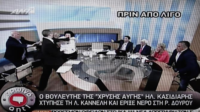 In this image taken off a TV screen, Ilias Kasidiaris, 2nd left, spokesman of Greece's extremist far-right Golden Dawn party, who was elected to Parliament in the country's recent inconclusive polls, physically assaults Liana Kanelli, a female member of the Parliament for the Greek Communist party, during a talk show at the studios of the ANTENA TV station in Athens on Thursday, June 7, 2012. Kasidiaris bounded out of his seat and slapped Kanelli three times after throwing a glass of water over radical left Syriza party member Rena Dourou. Police have issued an arrest warrant for Kasidiaris after he physically assaulted the two left-wing deputies on live television during a morning political show. (AP Photo/ANTENA TV)  TV OUT