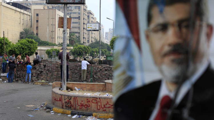 Supporters of ousted President Mohammed Morsi protest as army soldiers guard at the Republican Guard building in Nasr City, in Cairo, Egypt, Wednesday, July 10, 2013. (AP Photo/Hassan Ammar)