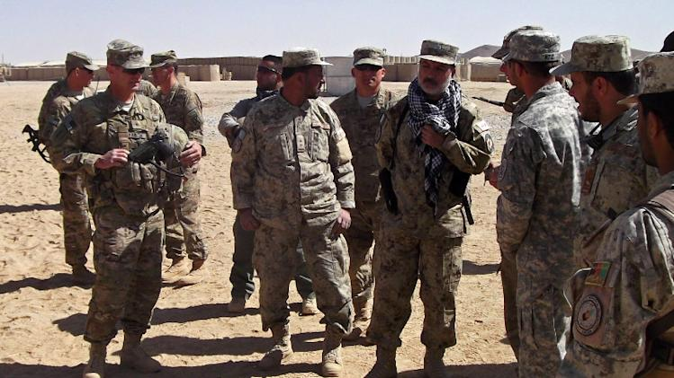This photo taken Oct. 10, 2012 shows Army Brig. Gen. John Charlton, left, foreground, talking to members of the Afghan National Civil Order Police at a military base in Ghazni Province, Afghanistan. A new chapter of the Afghanistan war is opening with a slimmed-down Western force doing more advising than fighting, a resilient Taliban showing little interest in peace talks, and Americans tempted to pull the plug on a conflict now in its 12th year. A decisive end seems nowhere in sight. (AP Photo/Robert Burns)